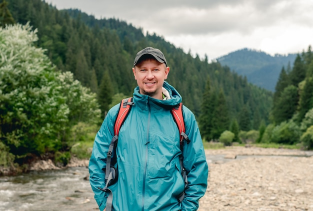 Uśmiechnięty turysta młody człowiek z plecakiem stojący na powierzchni góry rzeki