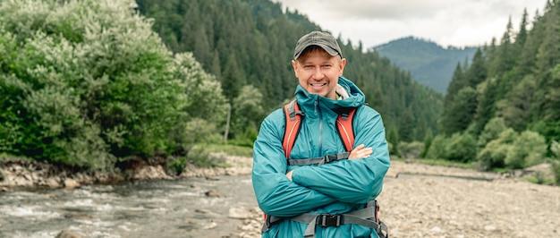 Uśmiechnięty turysta młody człowiek z plecakiem stojący na tle góry rzeki