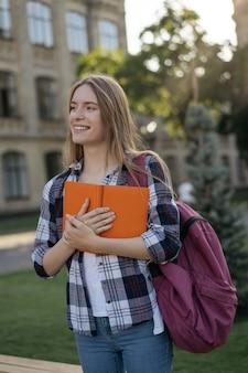 Uśmiechnięty uczeń chodzi z uniwersytetem z plecakiem i książką