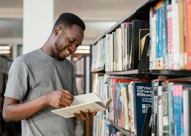 Uśmiechnięty uczeń czytanie książki średni strzał