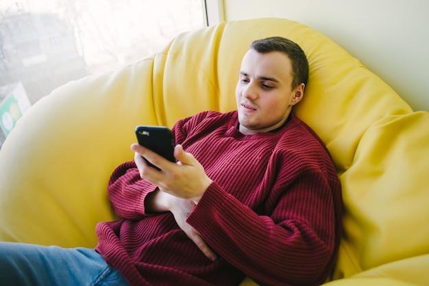 Uśmiechnięty uczeń odpoczywa podczas przerwy w żółtej fotelu i używa smartfona. rekreacja pasywna.