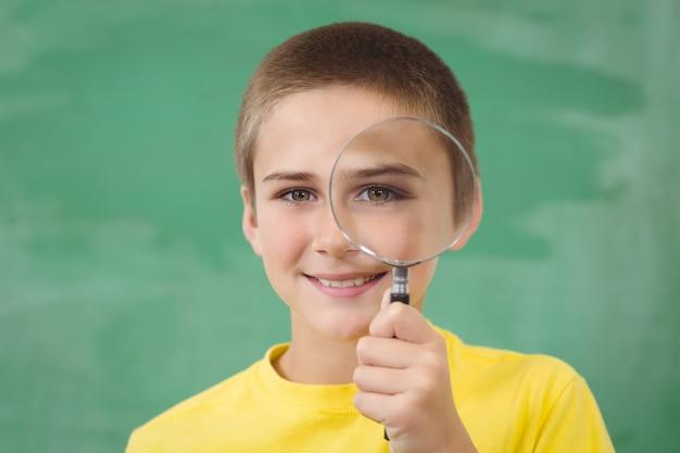Uśmiechnięty uczeń patrzeje przez magnifier w sala lekcyjnej