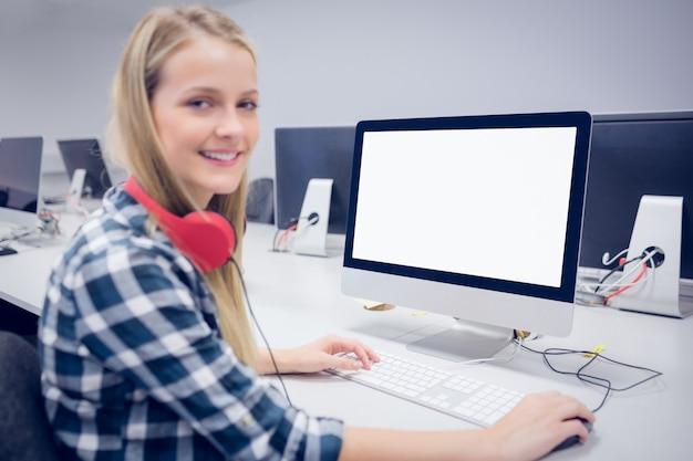 Uśmiechnięty uczeń pracuje na komputerze przy uniwersytetem