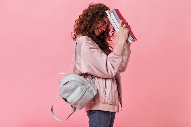 Uśmiechnięty uczeń trzyma książki i czuje się zdezorientowany