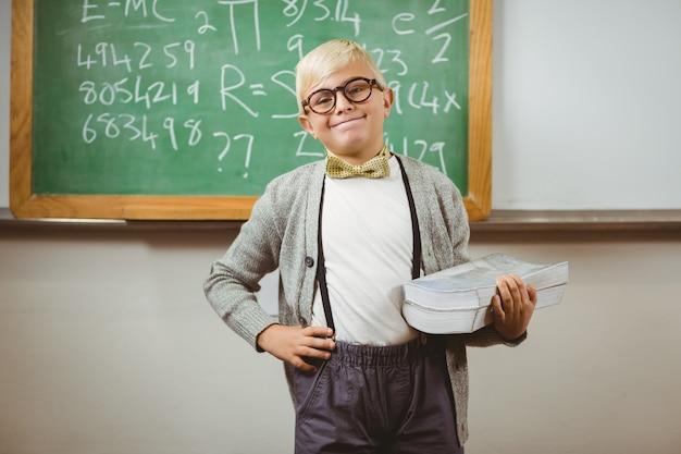 Uśmiechnięty uczeń ubierał up jako nauczyciela mienia książki