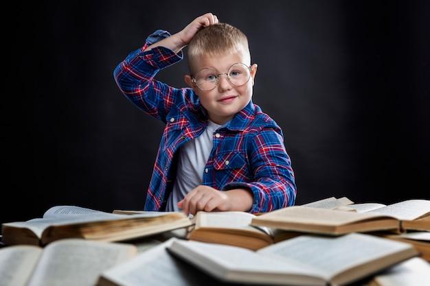 Uśmiechnięty uczeń w okularach siedzi przy stole ze stosem książek. szkolenie i wiedza. czarna przestrzeń.