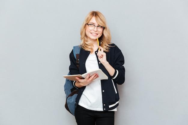 Uśmiechnięty uczeń z notatnikiem