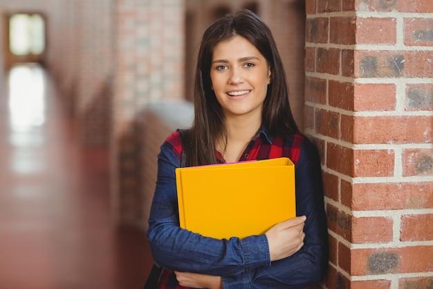Uśmiechnięty uczeń z segregatorem pozuje w korytarzu