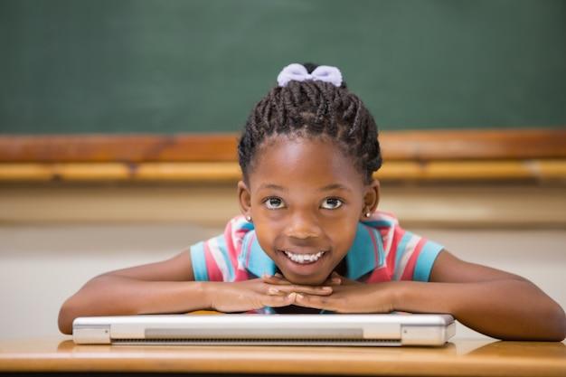 Uśmiechnięty ucznia obsiadanie przy jej biurkiem