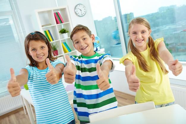 Uśmiechnięty uczniów z uniesiony