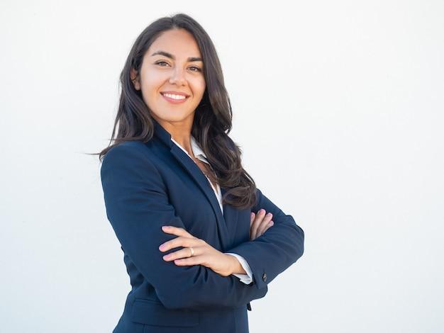 Uśmiechnięty ufny bizneswoman pozuje z rękami składać