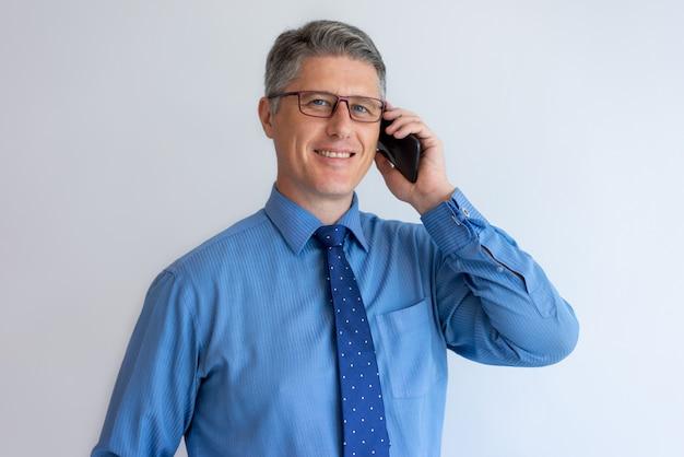 Uśmiechnięty ufny konsultant biznesowy opowiada klient