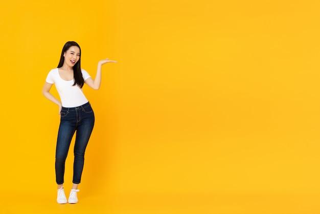 Uśmiechnięty ufny młody piękny azjatycki kobieta model robi otwartej dłoni gestowi