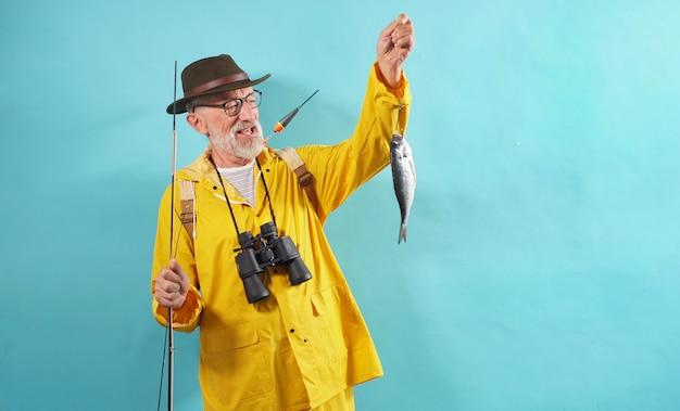 Uśmiechnięty, w okularach rybak ubrany w żółty płaszcz przeciwdeszczowy i zielony kapelusz trzyma swoją złapaną rybę na wędce, na białym tle, studio strzał