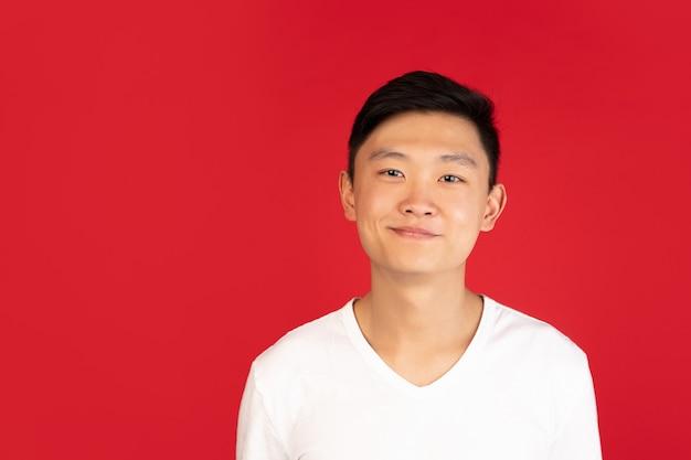 Uśmiechnięty, wesoły. portret azjatyckiego młodego człowieka na czerwonej ścianie. przystojny męski model w stylu casual. pojęcie ludzkich emocji, wyraz twarzy, młodość, sprzedaż, reklama.