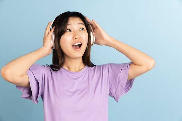 Uśmiechnięty, wesoły. portret młodej kobiety azjatyckie na niebieskiej ścianie. piękna modelka w stylu casual. pojęcie ludzkich emocji, wyraz twarzy, młodość, sprzedaż, reklama.