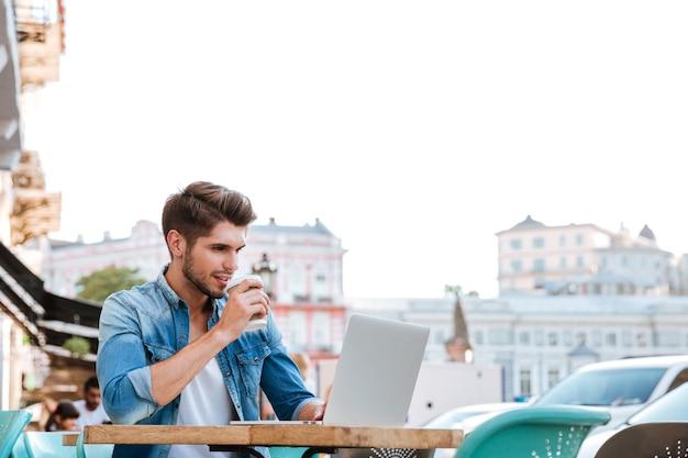 Uśmiechnięty wesoły przypadkowy mężczyzna korzystający z laptopa siedząc w kawiarni na świeżym powietrzu i pijący kawę