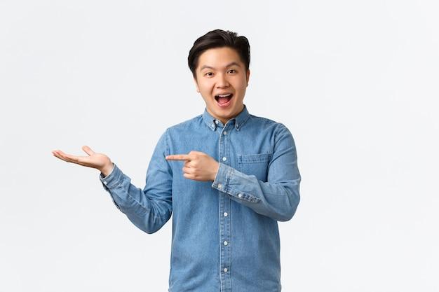 Uśmiechnięty Wesoły Słodki Azjatycki Mężczyzna Ogłaszający, Zademonstrował Nowy Produkt Pod Ręką, Wskazując Palcem Na Puste Miejsce Na Reklamę, Stojąc Rozbawiony Na Białym Tle. Premium Zdjęcia