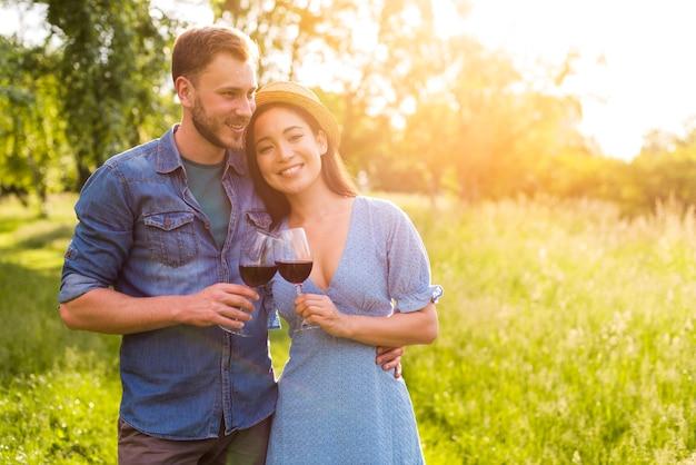 Uśmiechnięty wieloetniczny pary obejmowanie z szkłami w parku