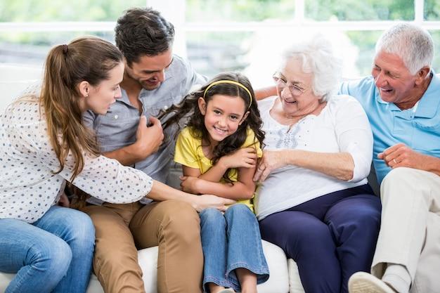Uśmiechnięty wielopokoleniowy rodzinny obsiadanie na kanapie