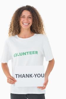 Uśmiechnięty wolontariusz pokazuje plakat z podziękowaniami
