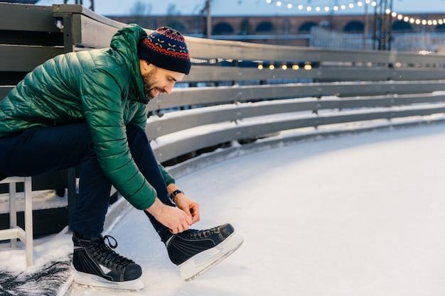 Uśmiechnięty, wspaniały mężczyzna sznuruje łyżwy, ćwiczy na lodowisku, jest w dobrym nastroju, lubi zimę i jeździ na łyżwach
