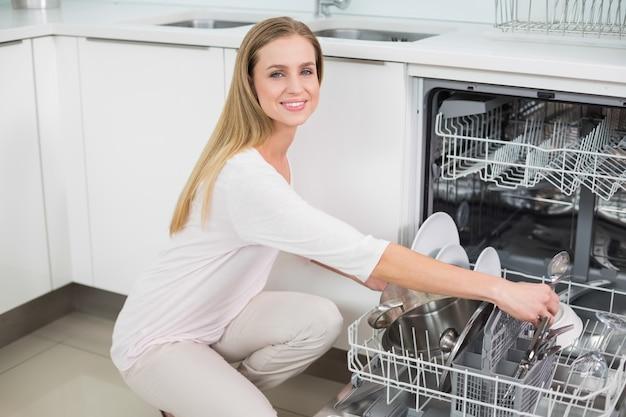 Uśmiechnięty wspaniały model klęcząc obok naczynia do mycia