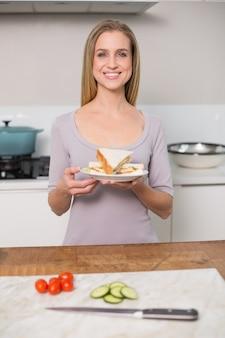 Uśmiechnięty wspaniały wzorcowy mienie talerz z kanapką