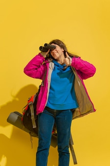 Uśmiechnięty, wygląda na szczęśliwego. portret wesoły młody turysta kaukaski dziewczyna z torbą i lornetką na białym tle na żółtym tle studio. przygotowanie do podróży. ośrodek wypoczynkowy, ludzkie emocje, wakacje.