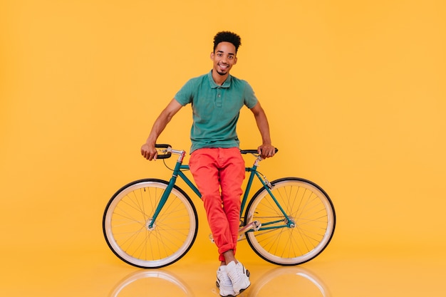 Uśmiechnięty wyrafinowany facet z czarnymi włosami pozuje z przyjemnością w pobliżu roweru. kryty portret entuzjastycznego afrykańskiego mężczyzny z zielonym rowerem.