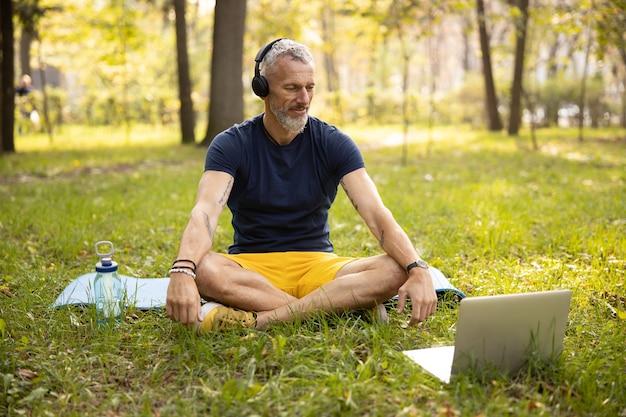 Uśmiechnięty wysportowany mężczyzna ćwiczący jogę online w naturze