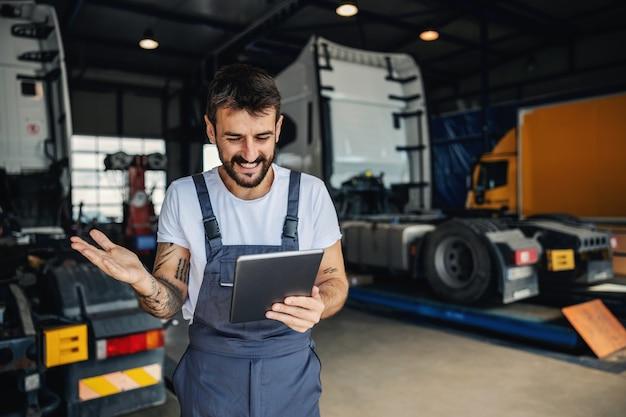Uśmiechnięty, wytatuowany, brodaty pracownik fizyczny w kombinezonie przy użyciu tabletu do sprawdzania dostawy, stojąc w garażu firmy importowo-eksportowej
