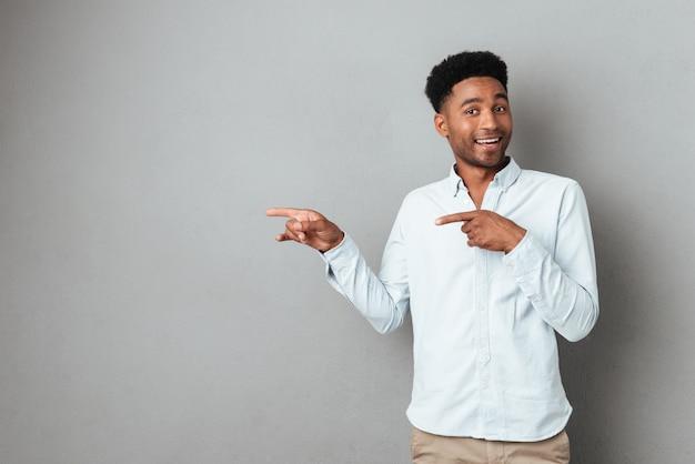 Uśmiechnięty z podnieceniem afrykański mężczyzna wskazuje palec daleko od