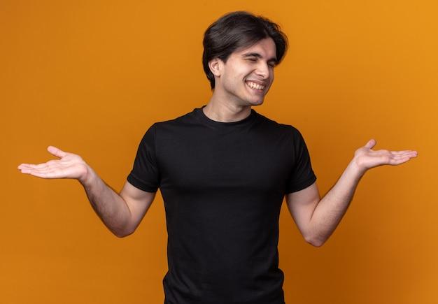 Uśmiechnięty z zamkniętymi oczami młody przystojny facet ubrany w czarną koszulkę, rozkładając ręce na białym tle na pomarańczowej ścianie
