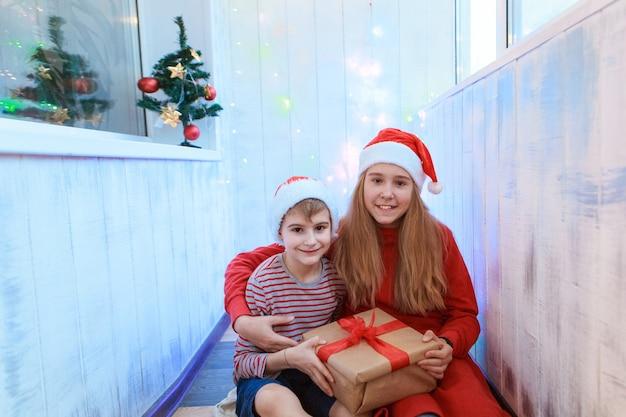 Uśmiechnięty zabawny dwoje dzieci w czerwonym kapeluszu santa gospodarstwa prezent na boże narodzenie w ręku. koncepcja nowego roku.