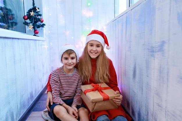 Uśmiechnięty zabawny dwoje dzieci w czerwonym kapeluszu santa, trzymając w ręku prezent na boże narodzenie. koncepcja nowego roku.