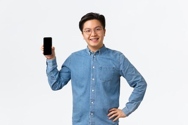 Uśmiechnięty zadowolony azjatycki freelancer, przedsiębiorca z własną małą firmą pokazujący zadowolony ekran smartfona. facet w szelkach i okularach korzystający z aplikacji mobilnej, białe tło