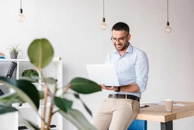 Uśmiechnięty zadowolony mężczyzna 30s ubrany w białą koszulę siedzi na stole w biurze i prowadzący biznesowy czat na srebrnym laptopie