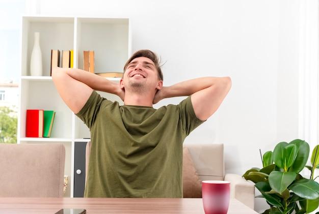 Uśmiechnięty zadowolony młody przystojny blondyn siedzi przy stole z kubkiem i telefonem, trzymając się za ręce razem na głowie, patrząc w górę w salonie