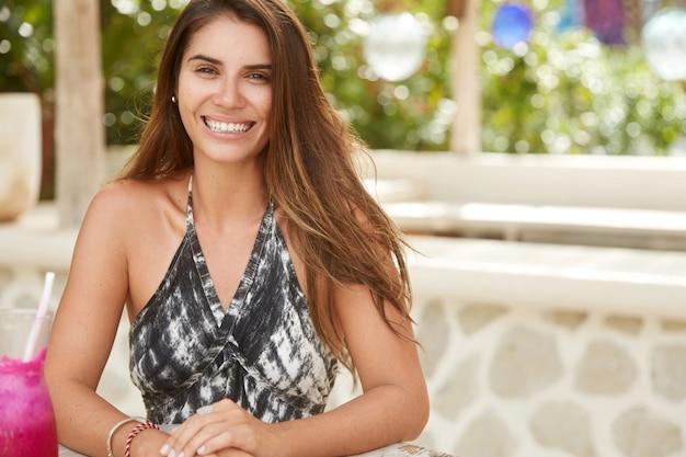 Uśmiechnięty zadowolony modelka o atrakcyjnym wyglądzie, pije smoothie w przytulnej kawiarni na świeżym powietrzu