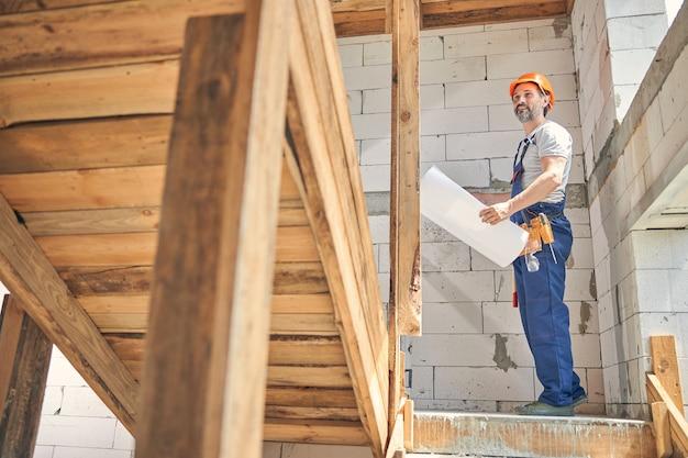 Uśmiechnięty zadowolony pracownik budowlany z projektem stojącym na schodach