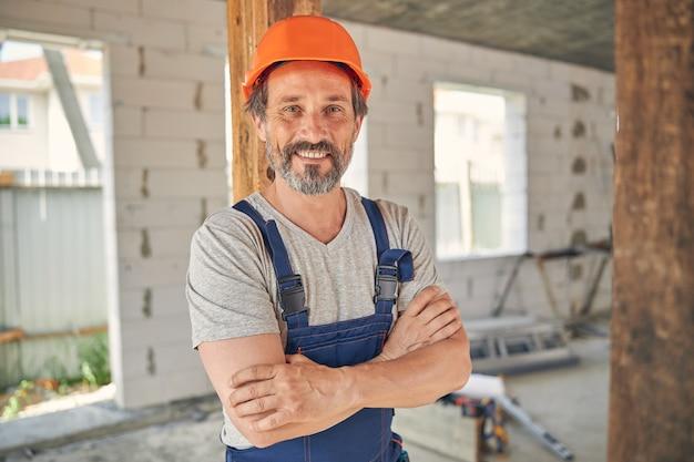Uśmiechnięty zadowolony pracownik płci męskiej z założonymi rękami pozuje do kamery