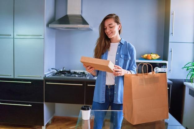 Uśmiechnięty zadowolony szczęśliwy dorywczo dorosły radosny młody tysiącletni klient dziewczyna otrzymał kartonowe torby z jedzeniem i napojami na wynos w domu. koncepcja usługi szybkiej dostawy