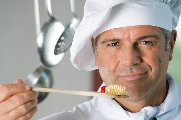 Uśmiechnięty zadowolony szef kuchni smakuje posiłek w restauracji
