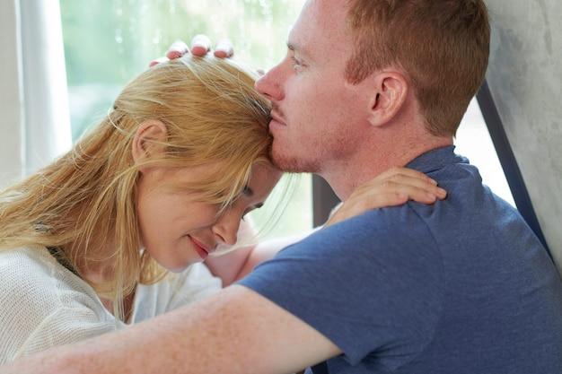 Uśmiechnięty Zamyślony Młody Człowiek Całujący Swoją Dziewczynę W Czoło I Cieszący Się Romantyczną Chwilą Premium Zdjęcia