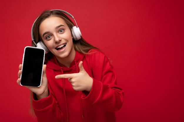 Uśmiechnięty zaskoczony piękna brunetka dziewczyna ubrana w czerwoną bluzę z kapturem na białym tle na czerwonej powierzchni gospodarstwa i