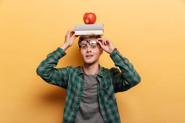 Uśmiechnięty zdumiony młody człowiek w okularach z książką i jabłkiem na głowie na żółtym tle