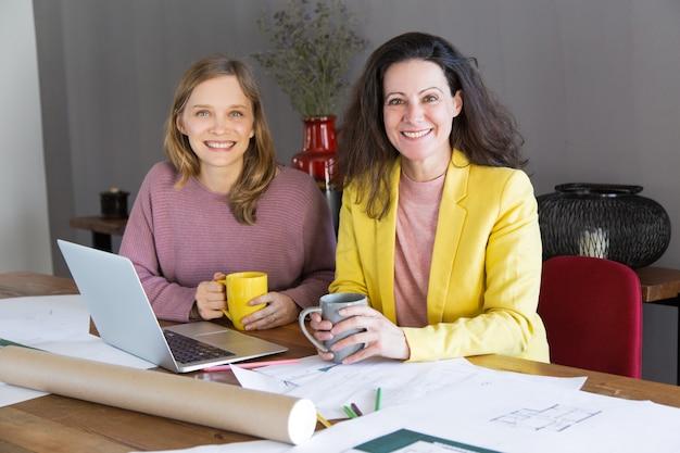 Uśmiechnięty żeński architekt i klient ma przerwę