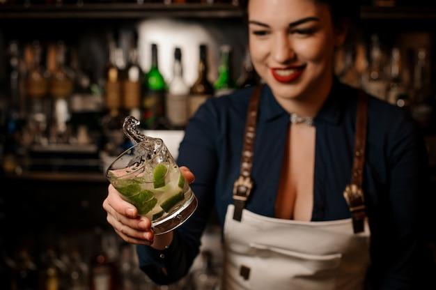 Uśmiechnięty żeński barman trzyma świeżego mojito koktajl
