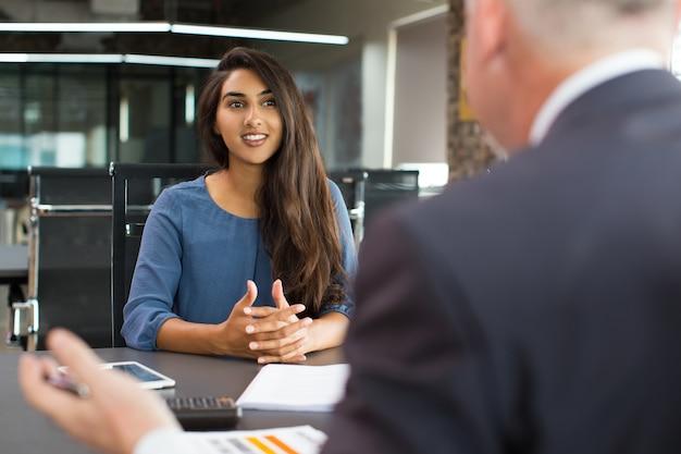 Uśmiechnięty żeński klient opowiada męski kierownik